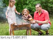 Купить «Молодой мужчина с дочерьми жарит курицу, грибы и сосиски на мангале», фото № 5691911, снято 2 июня 2013 г. (c) Losevsky Pavel / Фотобанк Лори
