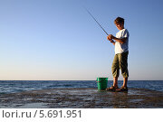 Купить «Мальчик с удочкой и ведром для рыбалки стоит на фоне моря и синего безоблачного неба», фото № 5691951, снято 22 августа 2013 г. (c) Losevsky Pavel / Фотобанк Лори