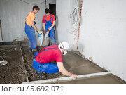 Трое рабочих заливают пол в комнате с черновой отделкой, фото № 5692071, снято 3 июля 2013 г. (c) Losevsky Pavel / Фотобанк Лори