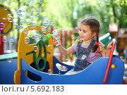 Купить «Маленькая девочка с косичками выдувает мыльные пузыри на детской площадке», фото № 5692183, снято 4 июня 2013 г. (c) Losevsky Pavel / Фотобанк Лори