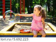 Купить «Маленькая девочка сидит на песочнице и надувает большой мыльный пузырь в солнечный день», фото № 5692223, снято 4 июня 2013 г. (c) Losevsky Pavel / Фотобанк Лори
