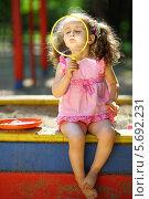 Купить «Маленькая девочка сидит на песочнице и пытается надуть большой мыльный пузырь», фото № 5692231, снято 4 июня 2013 г. (c) Losevsky Pavel / Фотобанк Лори