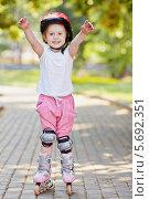 Купить «Маленькая девочка на роликах в защитных щитках стоит на дорожке в летнем парке, вытянув руки», фото № 5692351, снято 4 июля 2013 г. (c) Losevsky Pavel / Фотобанк Лори