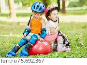 Купить «Мальчик и девочка на роликах сидят на гимнастическом мяче в парке», фото № 5692367, снято 4 июля 2013 г. (c) Losevsky Pavel / Фотобанк Лори