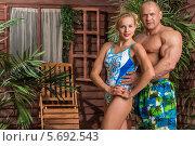 Купить «Девушка в купальнике и мускулистый мужчина позируют возле деревянного дома», фото № 5692543, снято 3 октября 2013 г. (c) Losevsky Pavel / Фотобанк Лори