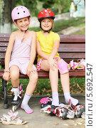 Купить «Две улыбающиеся девочки сидят на лавочке с роликовыми коньками», фото № 5692547, снято 8 июля 2013 г. (c) Losevsky Pavel / Фотобанк Лори