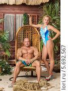 Купить «Девушка в купальнике и мускулистый мужчина, сидящий в плетёном кресле, возле деревянного дома», фото № 5692567, снято 3 октября 2013 г. (c) Losevsky Pavel / Фотобанк Лори