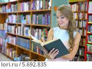 Купить «Улыбающаяся девушка с книгой в библиотеке», фото № 5692835, снято 22 июля 2013 г. (c) Losevsky Pavel / Фотобанк Лори