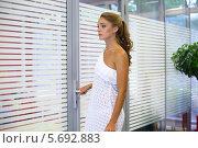 Купить «Девушка в белом платье стоит возле стеклянной двери», фото № 5692883, снято 22 июля 2013 г. (c) Losevsky Pavel / Фотобанк Лори