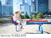 Купить «Девочка катается на карусели на фоне небоскребов», фото № 5692919, снято 21 июня 2013 г. (c) Losevsky Pavel / Фотобанк Лори
