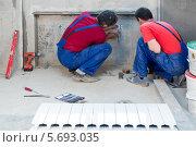Купить «Двое мужчин в спец одежде  устанавливают крепление для батарее под окном в квартире с черновой отделкой», фото № 5693035, снято 22 июня 2013 г. (c) Losevsky Pavel / Фотобанк Лори