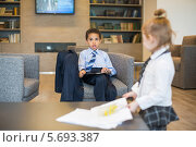 Купить «Мальчик и девочка в офисной одежде в интерьере бизнес-центра», фото № 5693387, снято 30 мая 2013 г. (c) Losevsky Pavel / Фотобанк Лори