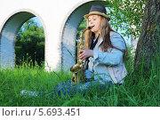 Купить «Девушка  в шляпе играет на саксофоне в парке в солнечный день», фото № 5693451, снято 6 июня 2013 г. (c) Losevsky Pavel / Фотобанк Лори