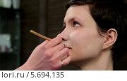 Стилист наносит тональный крем на лицо модели, видеоролик № 5694135, снято 10 февраля 2014 г. (c) Иван Артемов / Фотобанк Лори
