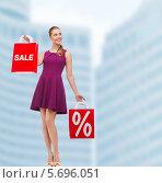 Купить «Счастливая девушка в платье и на высоких каблуках с покупками в руках», фото № 5696051, снято 12 февраля 2014 г. (c) Syda Productions / Фотобанк Лори