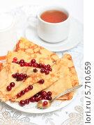 Купить «Блины с клюквой и чашка чая на столе», эксклюзивное фото № 5710659, снято 14 марта 2014 г. (c) Яна Королёва / Фотобанк Лори