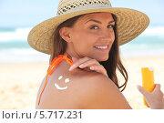 Купить «улыбающаяся молодая женщина наносит крем для загара», фото № 5717231, снято 13 июля 2010 г. (c) Phovoir Images / Фотобанк Лори