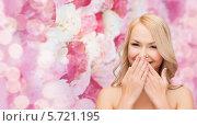 Купить «Счастливая девушка смеется, прикрыв рот ладонями», фото № 5721195, снято 7 января 2014 г. (c) Syda Productions / Фотобанк Лори