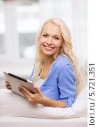 Купить «Улыбающаяся красивая девушка сидит дома на диване с планшетным компьютером», фото № 5721351, снято 6 февраля 2014 г. (c) Syda Productions / Фотобанк Лори