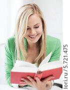 Купить «Улыбающаяся девушка-студентка читает книгу», фото № 5721475, снято 16 июня 2013 г. (c) Syda Productions / Фотобанк Лори