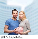 Купить «Улыбающиеся молодой человек и девушка держат большую розовую свинью-копилку», фото № 5721559, снято 9 февраля 2014 г. (c) Syda Productions / Фотобанк Лори