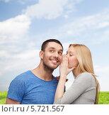 Купить «Молодой человек улыбается, слушая, что шепчет ему девушка по секрету на ухо», фото № 5721567, снято 9 февраля 2014 г. (c) Syda Productions / Фотобанк Лори