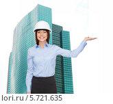 Купить «Деловая женщина в каске стоит на фоне небоскреба», фото № 5721635, снято 20 декабря 2013 г. (c) Syda Productions / Фотобанк Лори