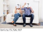 Купить «мужчина и женщина сидят на диване и держат знаки вопроса», фото № 5726107, снято 12 октября 2013 г. (c) Андрей Попов / Фотобанк Лори
