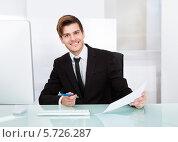 Купить «Портрет успешного бизнесмена с документами за столом в офисе», фото № 5726287, снято 19 октября 2013 г. (c) Андрей Попов / Фотобанк Лори