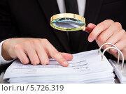 Купить «Бизнесмен читает документ с помощью увеличительной лупы», фото № 5726319, снято 19 октября 2013 г. (c) Андрей Попов / Фотобанк Лори