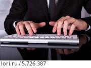 Бизнесмен печатает на клавиатуре за офисным столом. Стоковое фото, фотограф Андрей Попов / Фотобанк Лори