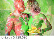 Купить «Измазанные в краске мужчина и женщина поедают апельсин в поцелуе», фото № 5728595, снято 11 мая 2013 г. (c) Losevsky Pavel / Фотобанк Лори