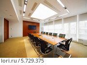 Купить «Длинный деревянный стол и черные кресла в светлой комнате для деловых переговоров», фото № 5729375, снято 22 мая 2013 г. (c) Losevsky Pavel / Фотобанк Лори