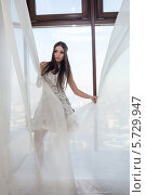Купить «Девушка в белом платье с цветами позирует возле окна с тюлевой занавеской», фото № 5729947, снято 16 декабря 2012 г. (c) Losevsky Pavel / Фотобанк Лори