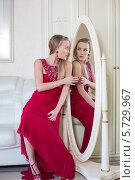 Купить «Красивая молодая девушка в красном платье сидит перед зеркалом», фото № 5729967, снято 16 декабря 2012 г. (c) Losevsky Pavel / Фотобанк Лори