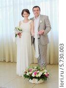 Купить «Жених и невеста стоят перед корзиной цветов на фоне занавесок», фото № 5730003, снято 10 мая 2013 г. (c) Losevsky Pavel / Фотобанк Лори