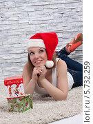 Веселая девушка в шапке Санта Клауса лежит на полу рядом с подарочными коробками на фоне каменной кладки. Стоковое фото, фотограф Daniil Nikiforov / Фотобанк Лори
