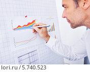 Купить «Бизнесмен анализирует график», фото № 5740523, снято 10 ноября 2013 г. (c) Андрей Попов / Фотобанк Лори