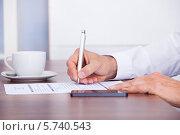 Купить «Бизнесмен заполняет бланк», фото № 5740543, снято 10 ноября 2013 г. (c) Андрей Попов / Фотобанк Лори