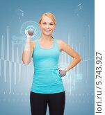 Молодая женщина со спортивной фигурой выполняет упражнения с гантелями на светлом фоне. Стоковое фото, фотограф Syda Productions / Фотобанк Лори