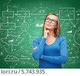Купить «Задумчивая молодая женщина стоит на фоне доски со схемами и формулами», фото № 5743935, снято 5 декабря 2013 г. (c) Syda Productions / Фотобанк Лори