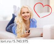 Красивая блондинка с планшетным компьютером лежит на диване дома. Стоковое фото, фотограф Syda Productions / Фотобанк Лори
