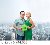 Купить «Улыбающиеся парень и девушка держат в руках зеленый бумажный дом на фоне современного города», фото № 5744055, снято 16 февраля 2014 г. (c) Syda Productions / Фотобанк Лори
