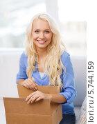 Купить «Счастливая девушка открывает дома посылку», фото № 5744159, снято 6 февраля 2014 г. (c) Syda Productions / Фотобанк Лори