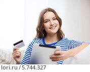 Купить «Привлекательная девушка с планшетным компьютером и кредитной пластиковой картой», фото № 5744327, снято 26 февраля 2014 г. (c) Syda Productions / Фотобанк Лори