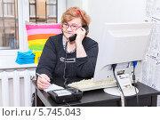 Купить «Женщина пенсионного возраста разговаривает по телефону за компьютером в офисе», фото № 5745043, снято 23 марта 2014 г. (c) Кекяляйнен Андрей / Фотобанк Лори
