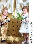 Мальчик в концертном костюме в стиле ретро с гитарой и девочка в белом платье с цветами и микрофоном. Стоковое фото, фотограф Losevsky Pavel / Фотобанк Лори