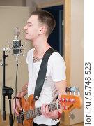 Молодой бас-гитарист играет и поет в студии звукозаписи. Стоковое фото, фотограф Losevsky Pavel / Фотобанк Лори