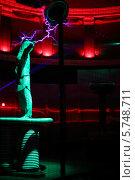 Купить «Мужчина в специальной одежде демонстрирует молнии на презентации аттракциона Мегавольт, ВВЦ, Москва, Россия», фото № 5748711, снято 8 февраля 2013 г. (c) Losevsky Pavel / Фотобанк Лори