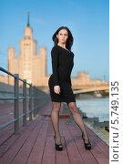Купить «Молодая женщина в черном платье и на высоких каблуках позирует на набережной», фото № 5749135, снято 26 мая 2013 г. (c) Losevsky Pavel / Фотобанк Лори